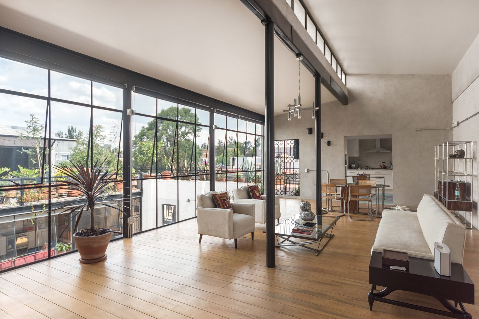 Living Room, Pendant Lighting, Sofa, Medium Hardwood Floor, and Chair The free height of the apartments allows a great entrance of daylight and ventilation.  Lirio 7