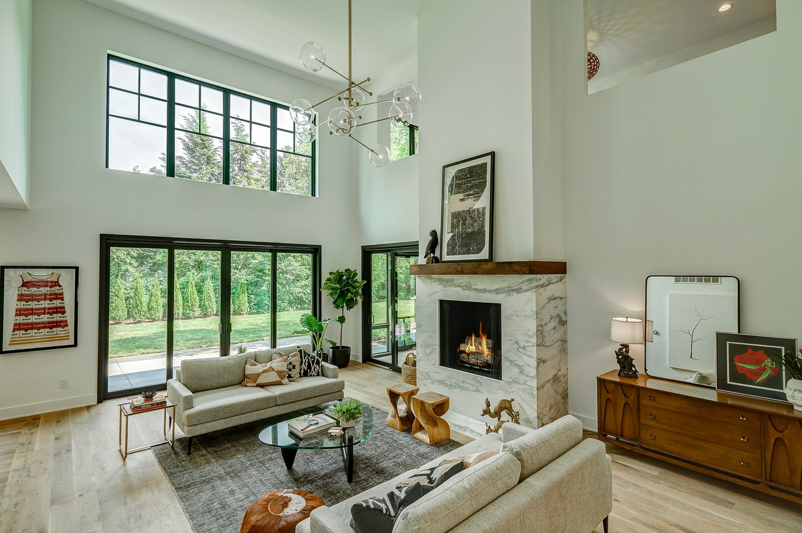 Living Room, Lamps, Stools, Accent Lighting, Coffee Tables, Sofa, Ceiling Lighting, Table Lighting, End Tables, Standard Layout Fireplace, Ottomans, Light Hardwood Floor, Gas Burning Fireplace, and Console Tables Dorchester Interior Great Room  The Dorchester Project by  Paul + Jo Studio
