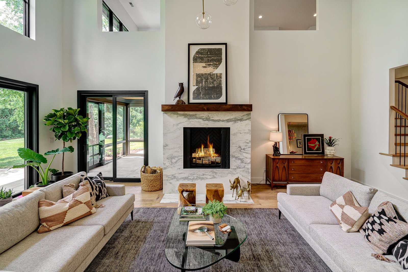 Living Room, End Tables, Lamps, Table Lighting, Console Tables, Ottomans, Accent Lighting, Coffee Tables, Sofa, Gas Burning Fireplace, Light Hardwood Floor, Standard Layout Fireplace, Ceiling Lighting, and Stools Dorchester Interior Great Room  The Dorchester Project by  Paul + Jo Studio