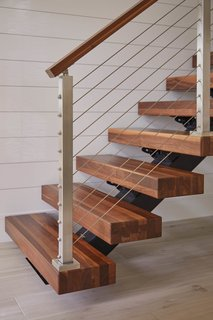 In traditional stairs construction, the stringers—or support—of a staircase are made out of lumber and built into the walls on either side of it. In this floating Viewrail stairway, a metal stringer supports the stairs from below.