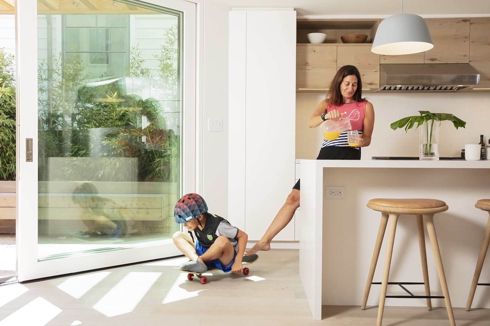 A woman with brown hair stands in a kitchen, pouring orange juice from a carafe into a glass. Her foot is out, holding on to the edge of a skateboard, on which a male child with a helmet sits, trying to scoot away. Behind them are the oak cabinets of the kitchen.