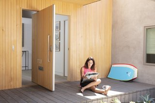 """A pivot door is one of the home's unique features. """"It's meant to be more seamless as far as coming in and out. There's drama in the way it hinges and in the scale of the door,"""" says architect Peter Liang."""