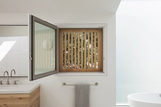 The slatted siding is not just an aesthetic choice, but also a practical one that provides privacy. The master bath features touch-latch cabinets and fixtures by California Faucets.