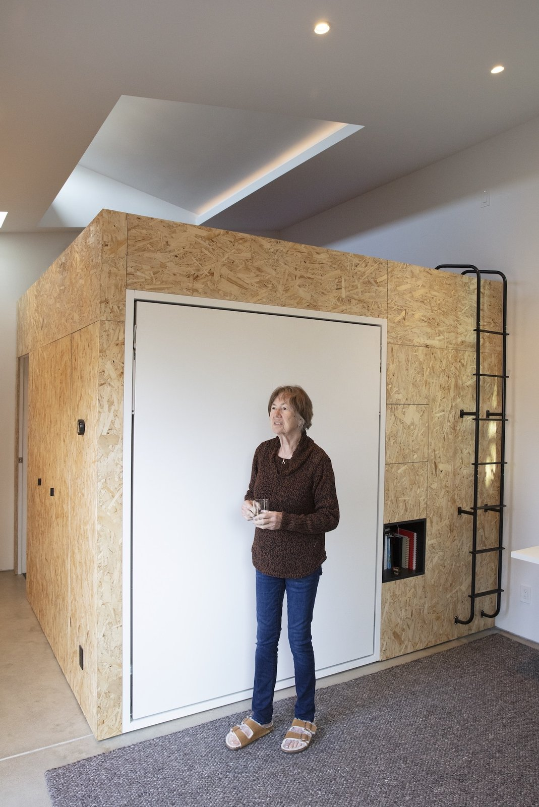 Living area with Murphy bed in a tiny house designed by Blue Truck Studio.