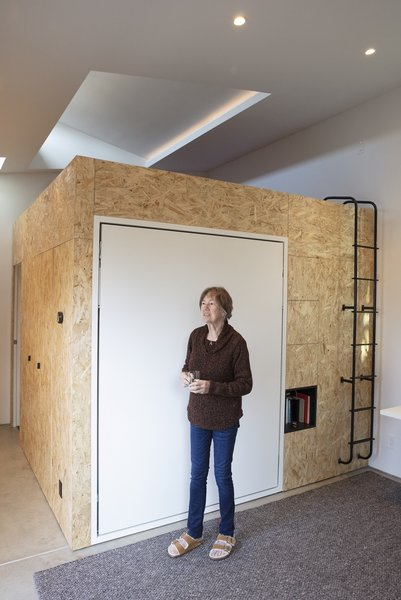 "Irmhild Liang stands in front of the Murphy bed, made by Resource Furniture, in the living area of her tiny home. ""Because we were designing for someone in their 80s, accessibility had to be acknowledged,"" Stefanie Liang Chung says. ""We were worried about the Murphy bed, but she tested it out, and she can do it on her own."""