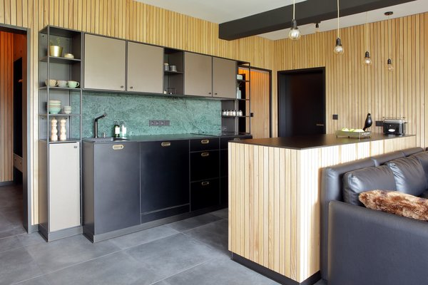 In a mountain retreat in the Czech Republic near the border with Germany, Martina Schultes designed a kitchen that brings the outside in, with wood plank paneling used on the walls and the kitchen island. The island and countertops are topped with black laminate, and the backsplash is a green marble, which stands out against the back cabinets.
