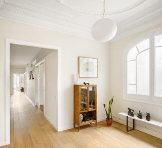 """""""The corridor was enlarged and the doors were replaced with large, white, lacquered wooden walls and sliding glass,"""" says designer Marina Sezam."""