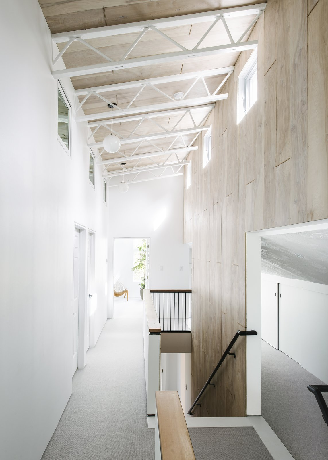 The birch plywood of the back stairs and loft ceiling is laid in a large tile pattern and stained with a varying amount of white sheen. Each line of tiling connects the spacing of the trusses to each stair tread to create a unified frame that one moves through.