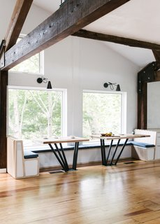 The kitchen banquet table consists of a white oak slab atop blackened steel pipes to create a light, rhythmic and robust composition.