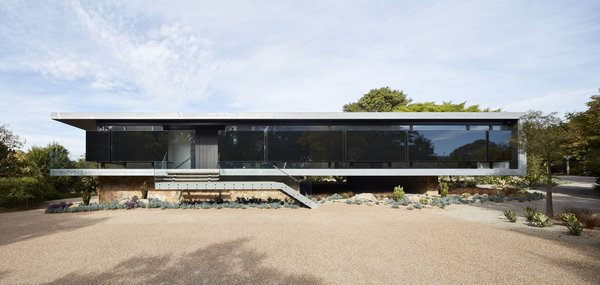 A look at the elevated west wall and entry. Here, insulated black panels spaced in glass cladding guard the home against harmful weather while reflecting beautiful silhouettes of the garden.