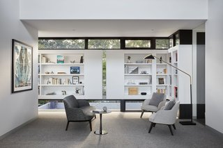 In the sitting area next to the bedroom wing, the exterior panels take the form of interior bookshelves. Framed with glass above, below, and between, the shelves allow nature to peek through.