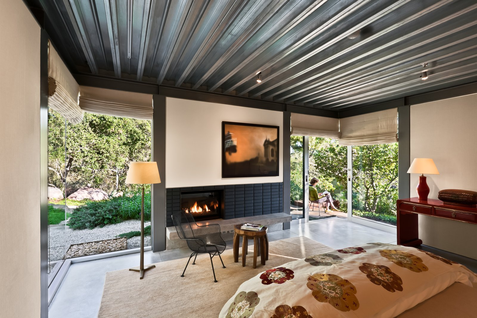 Bedroom, Bed, Concrete Floor, Chair, Floor Lighting, Dresser, Rug Floor, Ceiling Lighting, and Accent Lighting The second wing features both bedrooms each with clerestory windows to capture the natural light in sunny Montecito and frame the magnificent views.   Iconic Modernism by Barton Myers