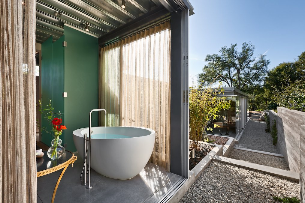 Bath Room, Freestanding Tub, and Concrete Floor Each bedroom is complete with en-suite baths. Both include clerestory windows that capture the natural light and embrace the stunning views.  Iconic Modernism by Barton Myers