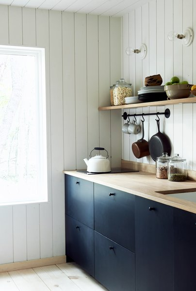 Dark cabinets juxtapose with white shiplap in this simple, functional kitchen. Solar power supplies the electric range top.