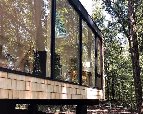 The retreat's exterior is clad in cedar shingles to give it a tree house feel. The shingles will weather to gray over time. Dutton wanted to avoid having the cabin stand out, instead revealing itself gradually against the surrounding landscape.