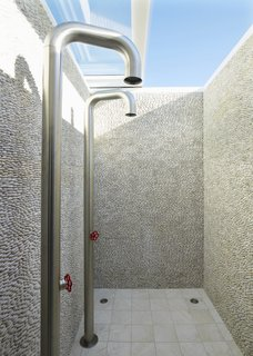 Thousands of river pebbles are stacked to create a unique look in this shower in the master suite. Boffi pipe shower fixtures lend an industrial look.