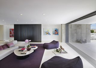Floor-to-ceiling windows are seen throughout the home, providing ample natural light. In the playroom, eggplant-colored seating and area rug add a touch of whimsy to this otherwise neutral-toned space.