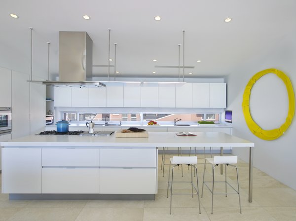 This light, airy, state-of-the-art kitchen sits at the front of the home, looking into the living area. Gaggenau appliances pair with a dramatic, stainless-steel oven hood. A bright yellow wall sculpture by Brad Howe channels the sun, adding visual interest, while white Corian countertops keeps the space feeling sleek.