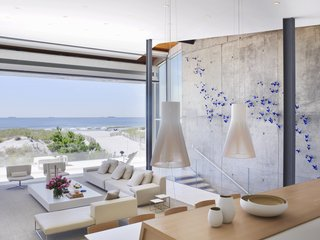 The main living space enjoys unfettered ocean views thanks to the beachfront location and the open glass door. Materials used in the home are decidedly weatherproof, like the travertine floors, the concrete thermal mass wall that runs the length of the home, and even the hardware on most of the furniture. Glass railings along the patio cut down on blowing sand and provide a measure of safety.