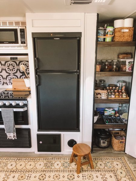 A small refrigerator and well-organized pantry outfit the kitchen.