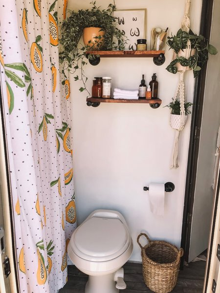 Adding life but not clutter, Jacqueline has adorned the RV with lots of greenery; a papaya-print shower curtain echoes the tiny home's plant life. A woven trash can and wood shelving give the room a chic, organic touch.