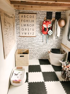 Brayden's playroom, located under his lofted bed, is clad in black-and-white foam tiles and a coordinating accent wall.