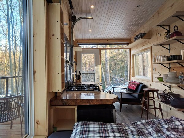 Each cabin comes equipped with a fully functional kitchen. Above, a wooden countertop echoes the hand-hewn, reclaimed wood on the walls, which was provided by John Loerchner's brother.