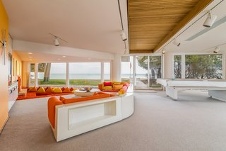 The downstairs recreation area of this William Kessler–designed home has plenty of playful features. The lower shag carpeted area features a unique retro sectional sofa that plays with oranges and yellows.