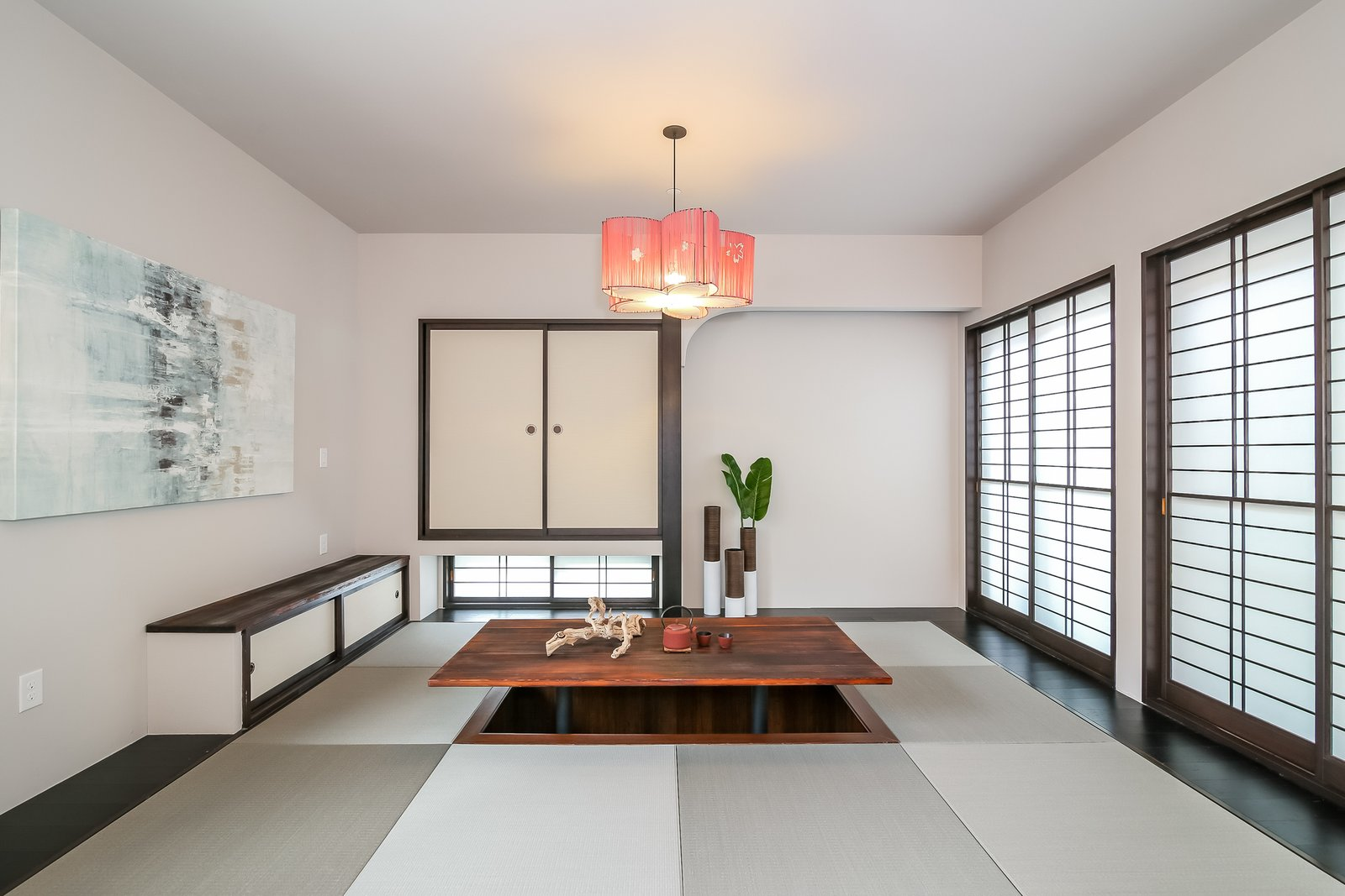 Living Room, Pendant Lighting, and Medium Hardwood Floor The den features a Japanese-style tatami tea room with enough space for up to 12 people to sit.  Japanese Builder Ichijo Creates Net-Zero Energy Home by PlanOmatic