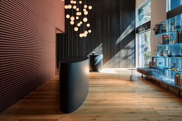 """In the reception area, Bocci Lights hang before a mesmerizing custom 3D wall by Bedots Architectural Surfaces. A bespoke metal """"curtain"""" by Baranowitz + Kronenberg lines the far wall. To the right is the hotel's shop, which exhibits books, housewares, and accessories by local brands."""