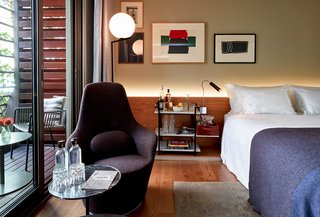 Sir Victor's rooms and suites were conceived by Sir Hotels' in-house design team. This bedroom pairs a Harbor chair by B&B Italia with handmade rugs by Nani Marquina and paintings by local artist Bernat Daviu.