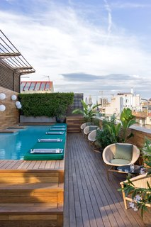 The rooftop pool strikes tropical vibes with cane furniture and palms.