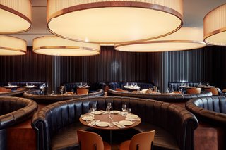 Immense cylindrical lights hang over semi-circular banquette seating in Mr. Porter.