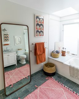 The master bathroom is filled with colorful textiles and quirky art.