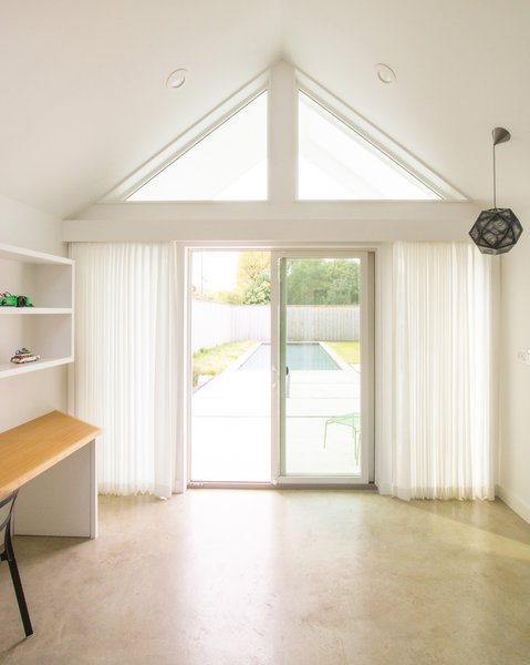 Official LLC installed a built-in desk and bed platform in Pool House. The high windows offer a glimpse out to the backyard, and curtains provide privacy when desired.