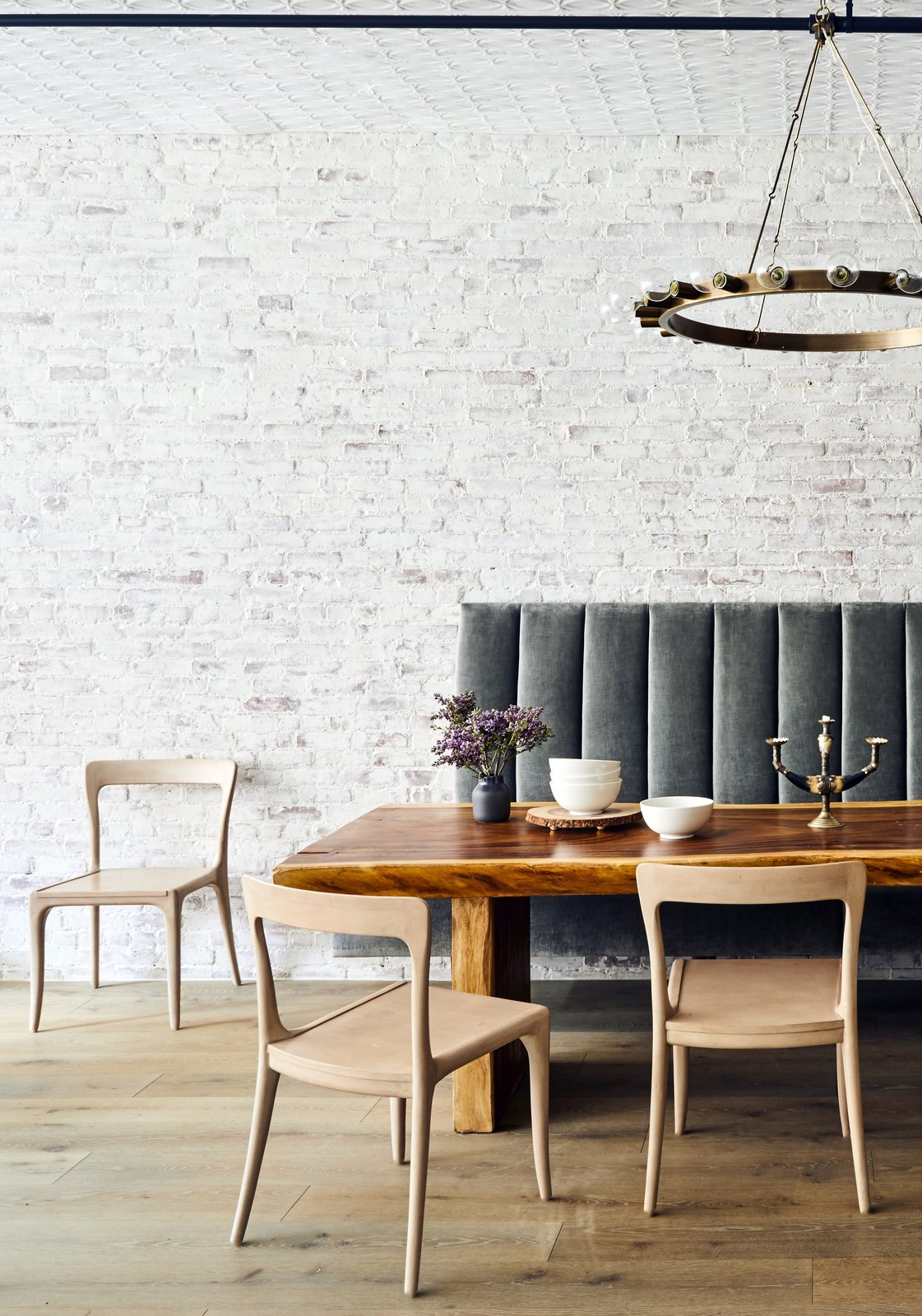 Dining, Light Hardwood, Chair, Table, Bench, and Pendant A custom designed built-in tufted banquette creates a soft, lush seating area at the live edge dining table. The velvet upholstery contrasts the exposed white-washed original brick in both texture and era. Overhead a brass chandelier with exposed Edison bulbs references the former Swan Incandescent Electric Light Co.  which occupied the loft after construction was completed in 1897.  Best Dining Bench Light Hardwood Pendant Photos from Crosby Loft