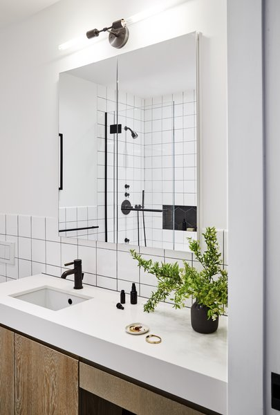 Both bathrooms feature subway tile, distressed white oak cabinetry and Edison Bulb light fixtures.