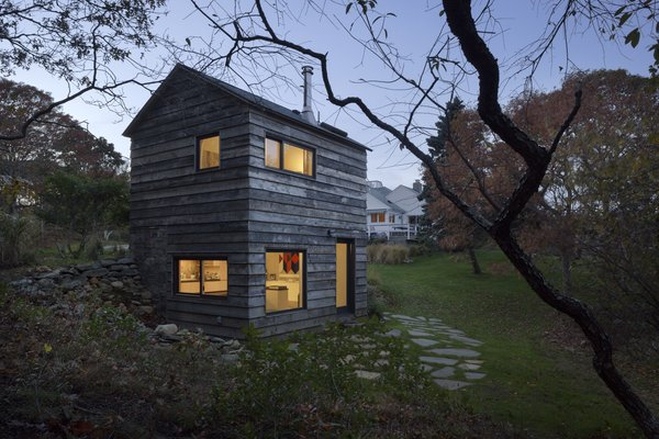 A reclaimed hickory wood facade punctured by windows overlooking the National Forest Service land