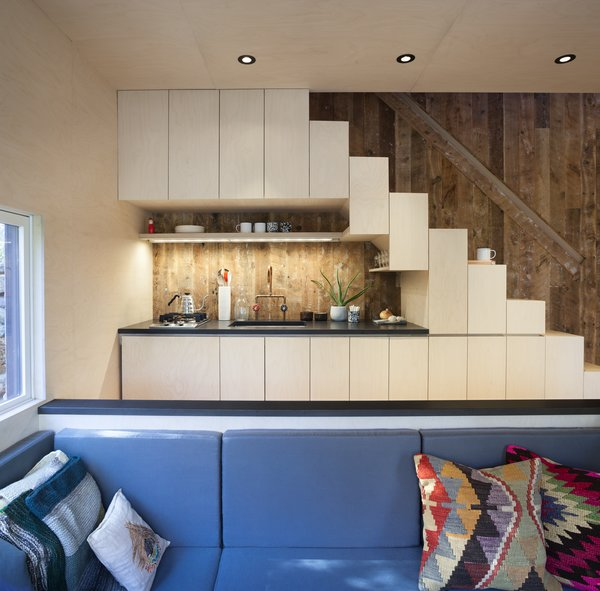 A micro kitchen tucked in under the open stair, with operable cabinets functioning as stair treads.