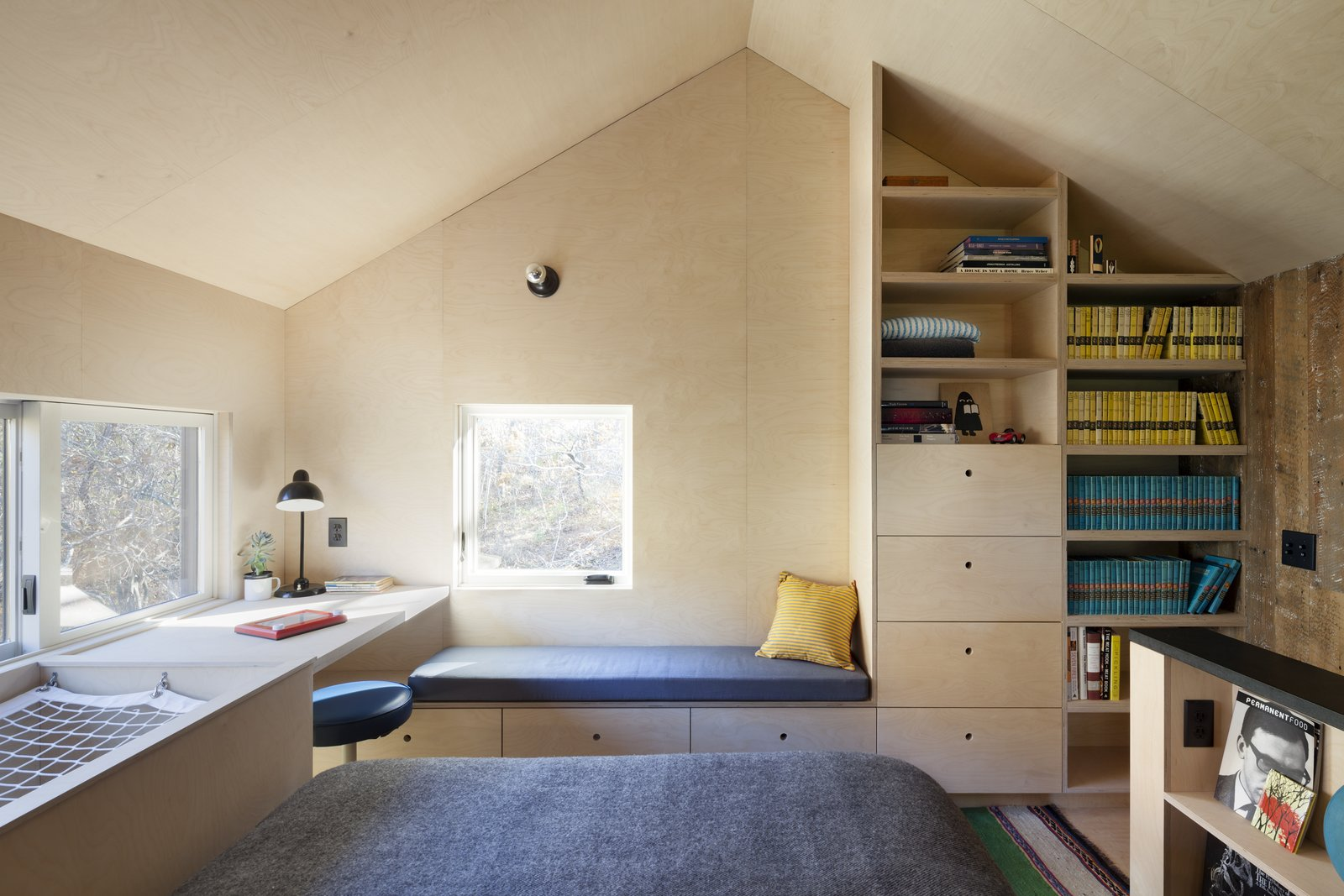 Bedroom, Plywood Floor, Bench, Bed, Shelves, and Wall Lighting The open bedroom at the second floor with built-in desk and shelving. The double height space at image left contains netting which supports the body, providing a spot for a floating perch above the entry.  Micro Cabin