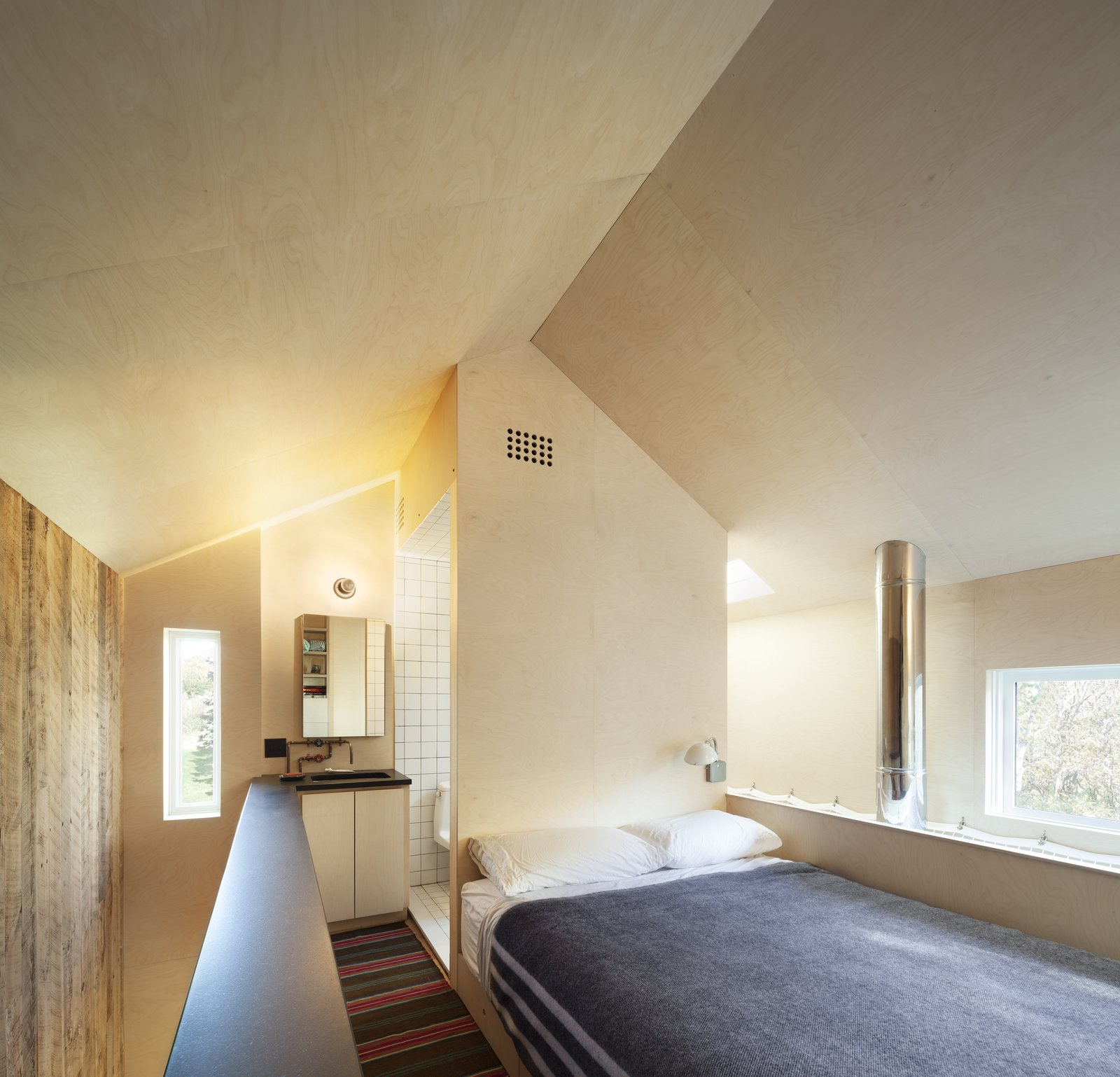 Bedroom, Wall Lighting, Plywood Floor, and Bed The bedroom with open bathroom behind. The volume of the bathroom shears the open geometry of the gabled roof form.  Micro Cabin