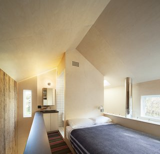 The bedroom with open bathroom behind. The volume of the bathroom shears the open geometry of the gabled roof form.