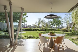 The indoor/outdoor living room features a table by BD Barcelona, chairs by E15, and a saucer-like pendant by Viabizzuno.