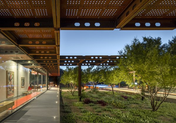 The perforated steel roof, made from Cor-Ten steel, offers much-needed shade for the house and courtyard.