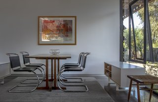 The study has a Nakashima table, MR chairs by Knoll and a Robert Rauschenberg print.