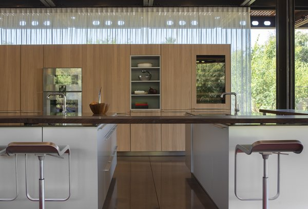 The kitchen features cabinetry by bulthaup and a walnut extendable bar.