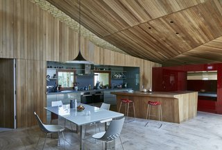 The kitchen and dining space has a limestone floor, an island made of solid iroko wood, and unit doors are made from MDF panels. The table, chairs, and barstools are by Calligaris.