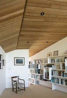 The library features bespoke shelving built by Featherstone Young and natural sisal carpeting.