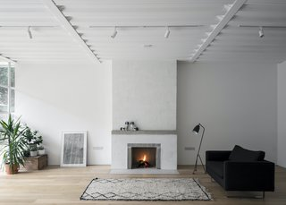 The main open-plan living space features a sofa from The Conran Shop, a vintage rug from SCP, a Grasshopper floor lamp by Gubi from Haus, two porcelain dogs from a charity shop, and a painting bought at the Royal Academy summer exhibition.