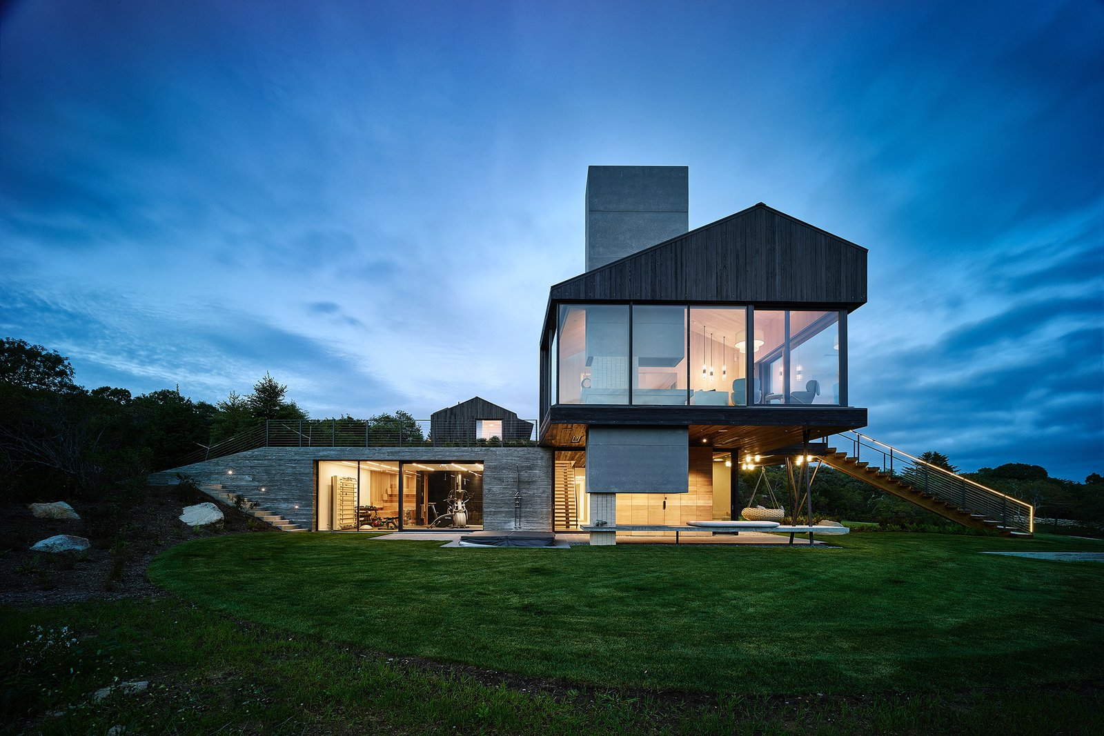 Exterior, House Building Type, Concrete Siding Material, Glass Siding Material, and Wood Siding Material Elevation looking out over the sheepfold. The cantilevered living room extends over an outdoor fireplace and sitting area, and the smokestack extends through.   Chilmark House